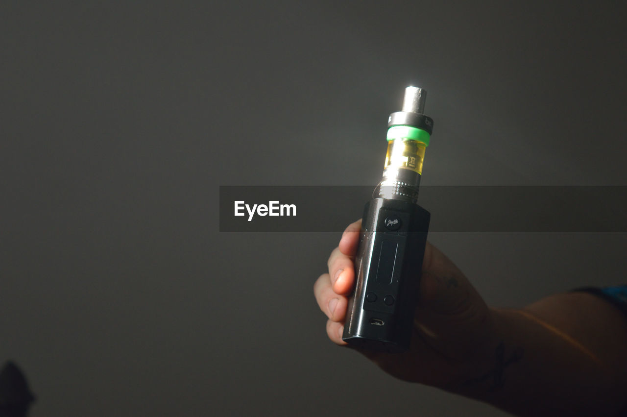 Cropped Image Of Hand Holding Electronic Cigarette Against Wall