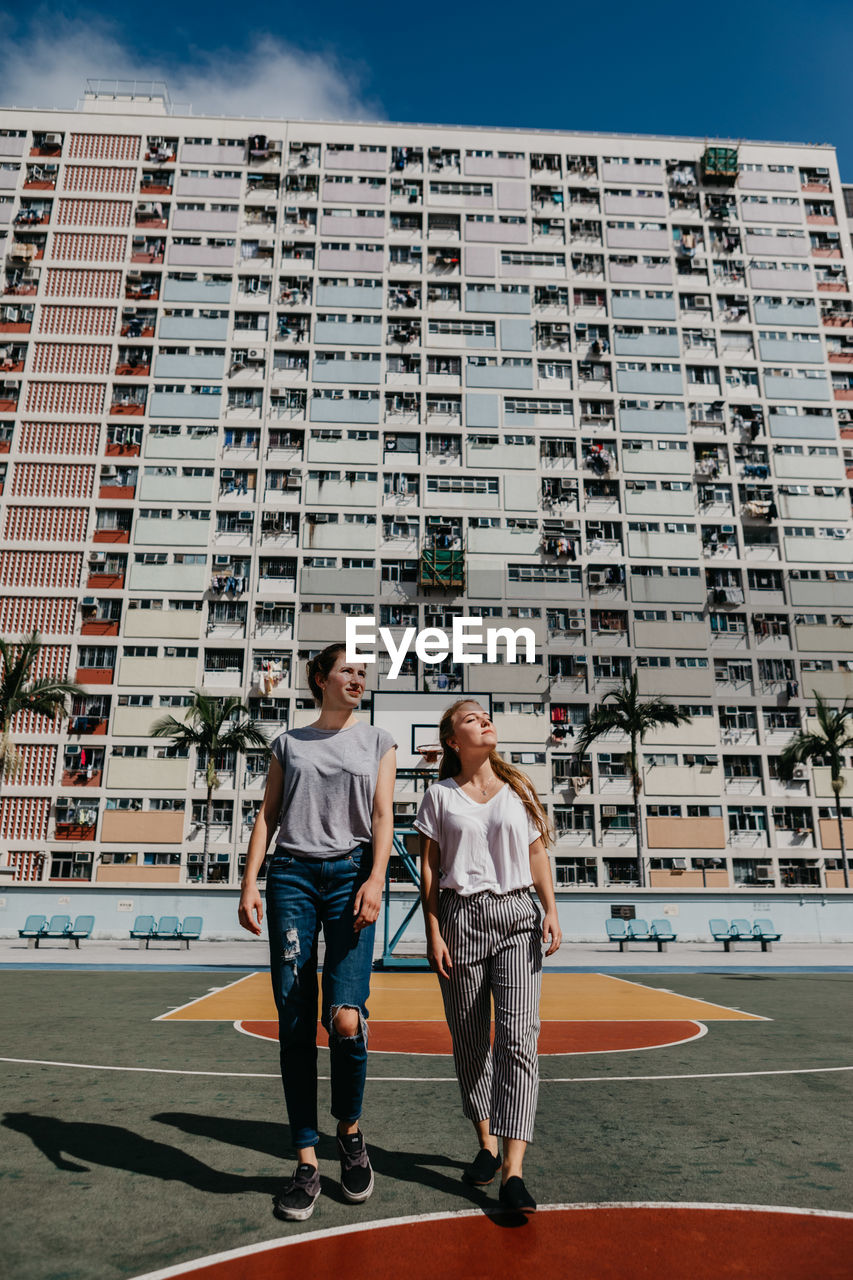 Friends Walking Against Buildings In City