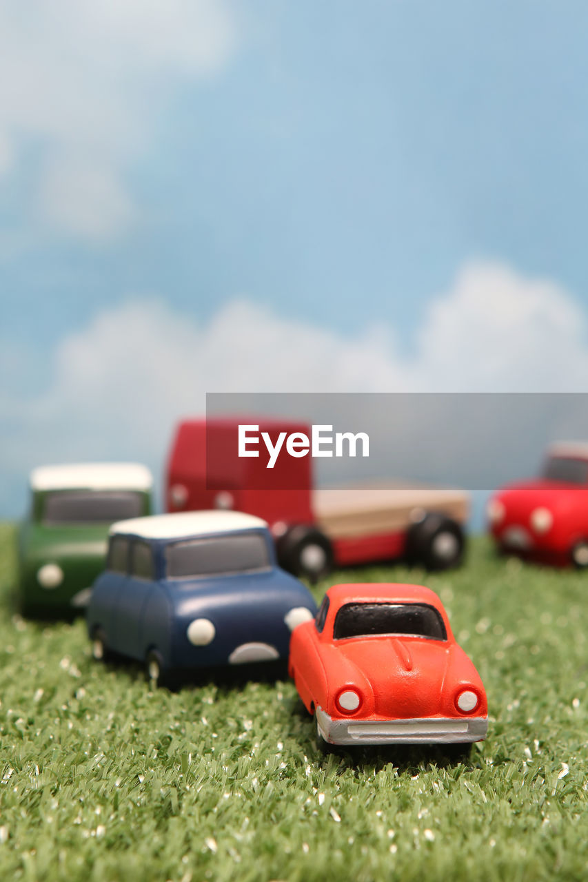 red, toy, car, toy car, no people, cloud - sky, mode of transportation, selective focus, transportation, day, nature, motor vehicle, close-up, sky, still life, land vehicle, grass, outdoors, green color, surface level