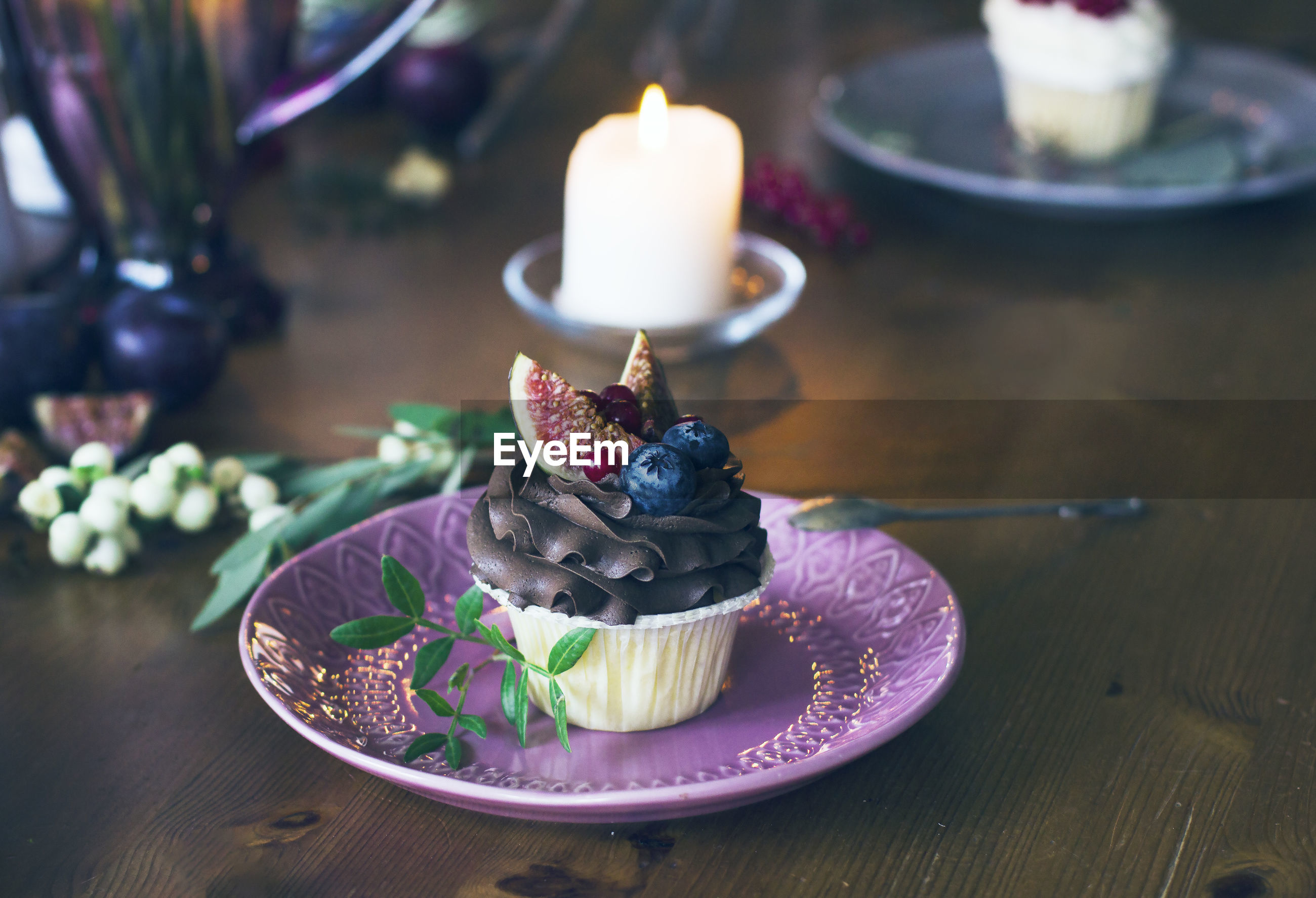 Tea light candles and cupcake in plate on table