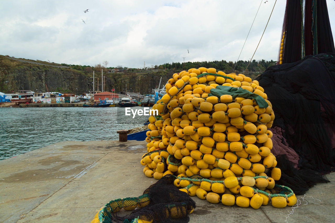 Buoys by fishing nets on pier by river