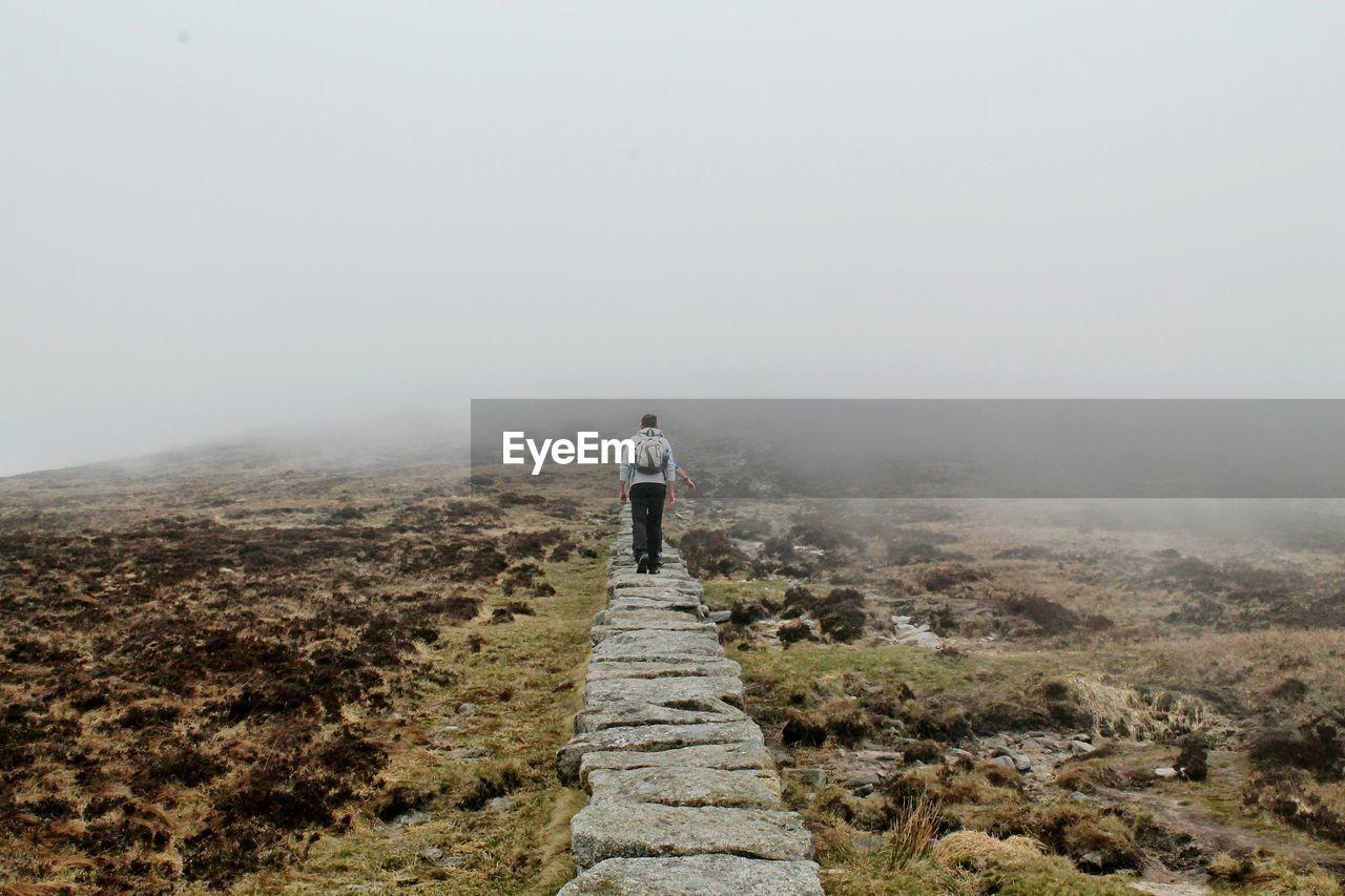 Rear View Of Man Walking On Stone Walk