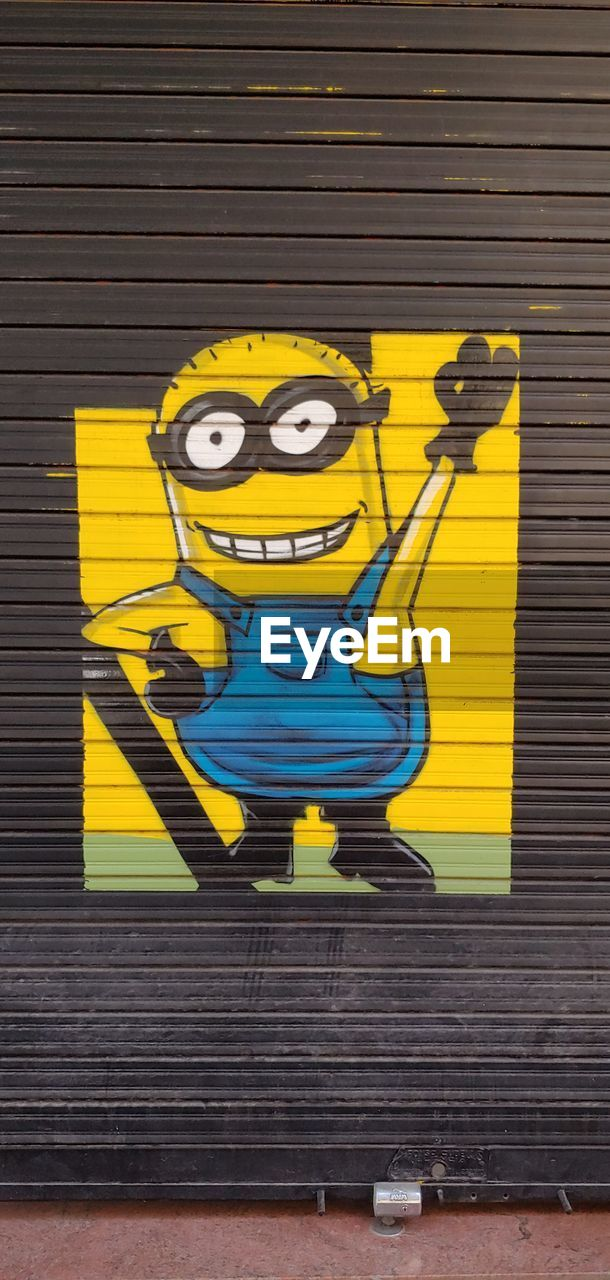 representation, yellow, creativity, art and craft, graffiti, human representation, wall - building feature, outdoors, day, wood - material, wall, no people, shutter, architecture, city, metal, close-up, male likeness, mural