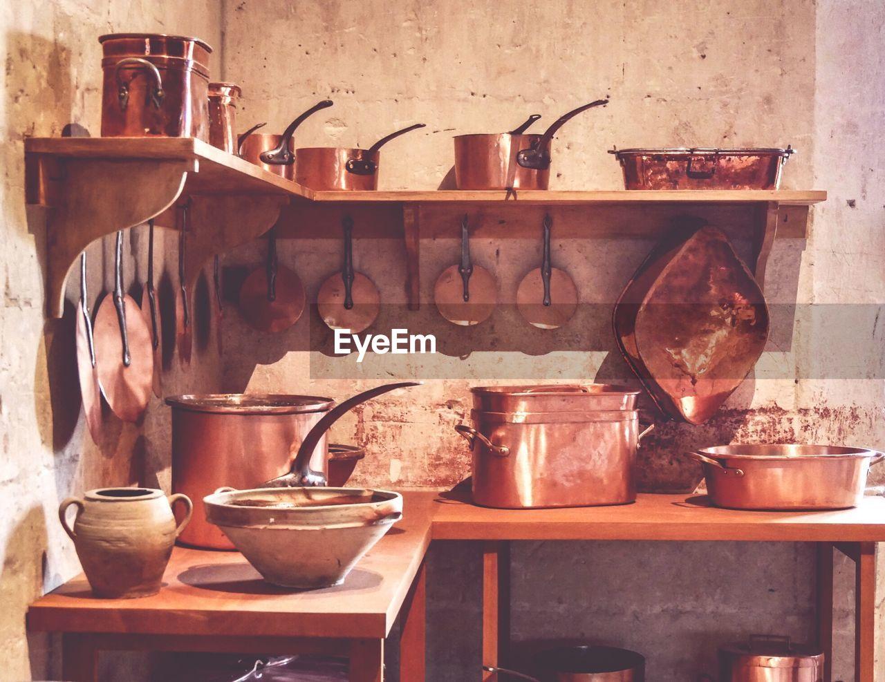 Utensils arranged on shelf in kitchen