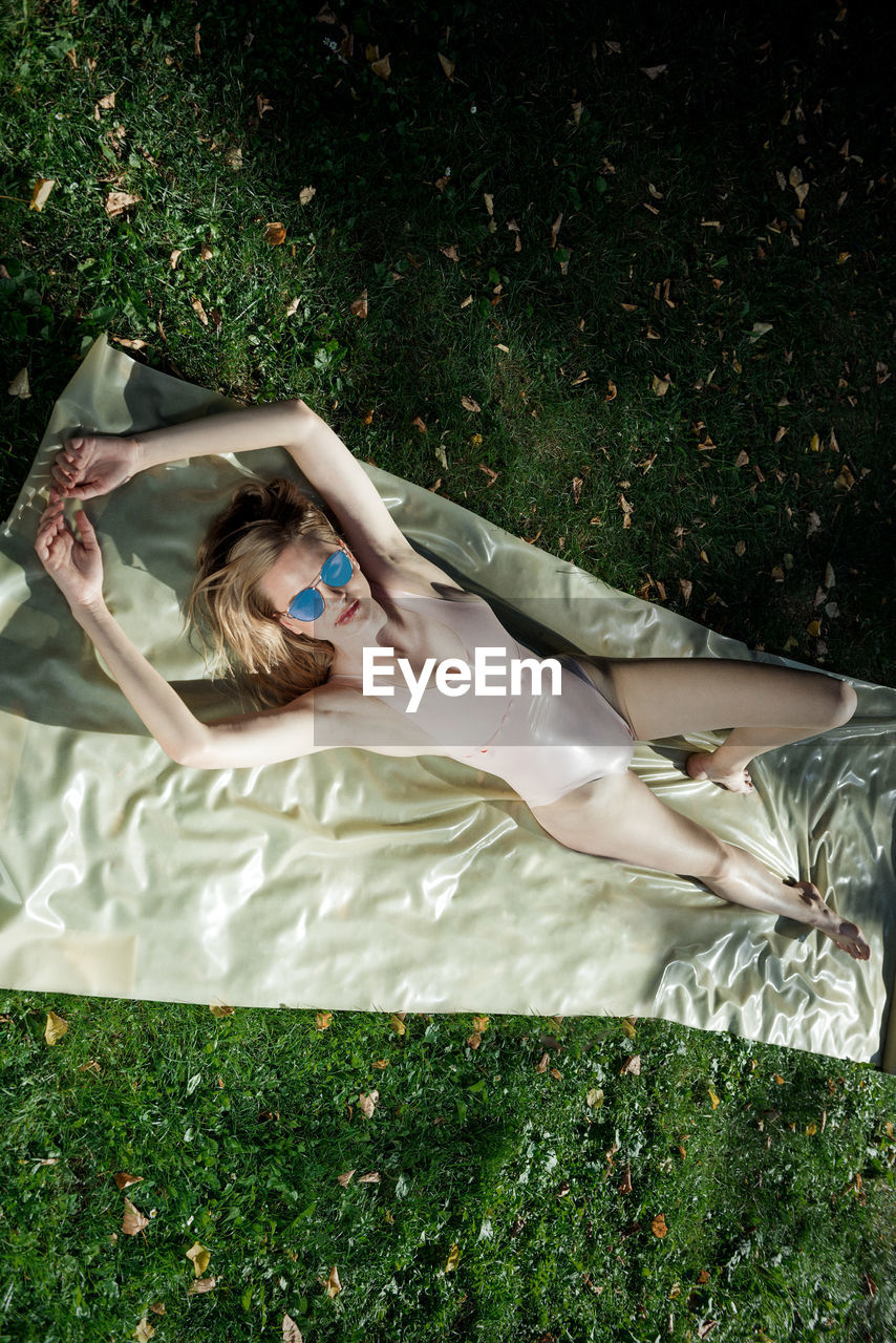 High Angle View Of Young Woman Wearing Swimsuit Lying On Field