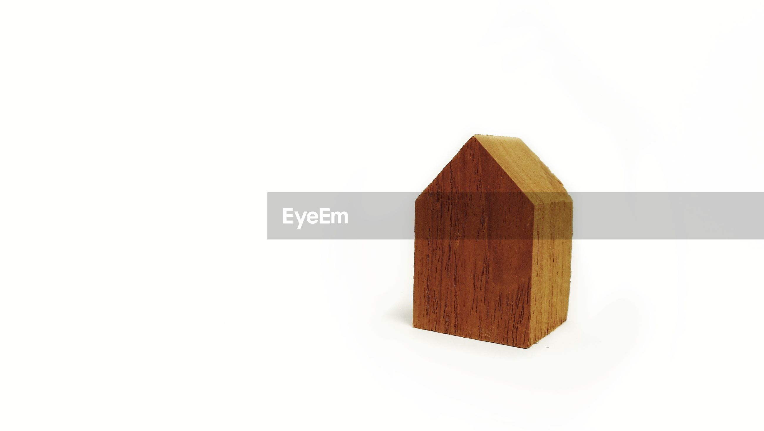 Close-up of wooden toy block over white background