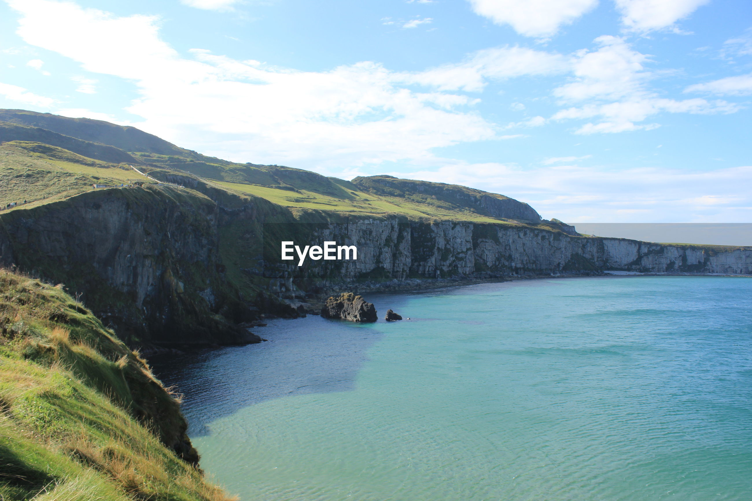 SCENIC VIEW OF SEA BY LANDSCAPE AGAINST BLUE SKY