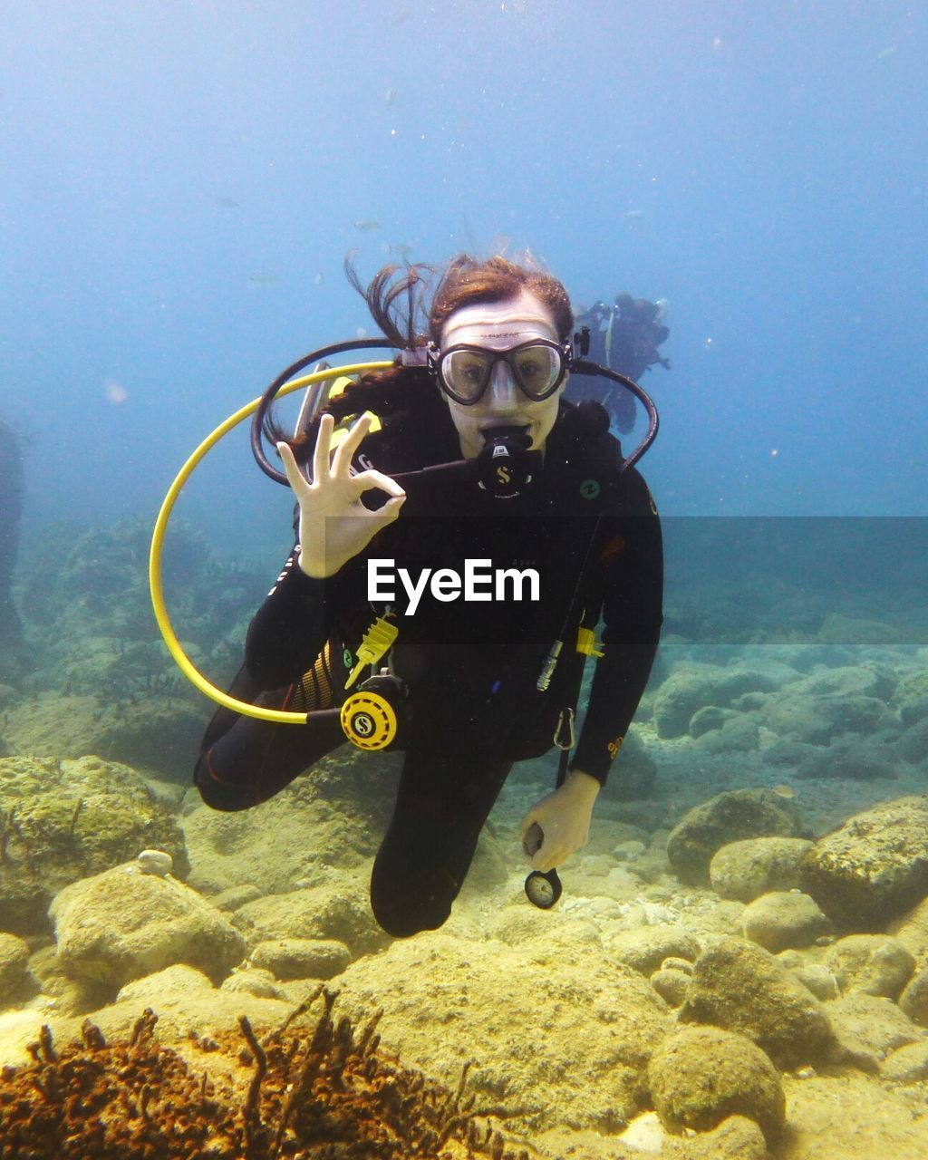 Portrait Of Young Woman Gesturing While Scuba Diving