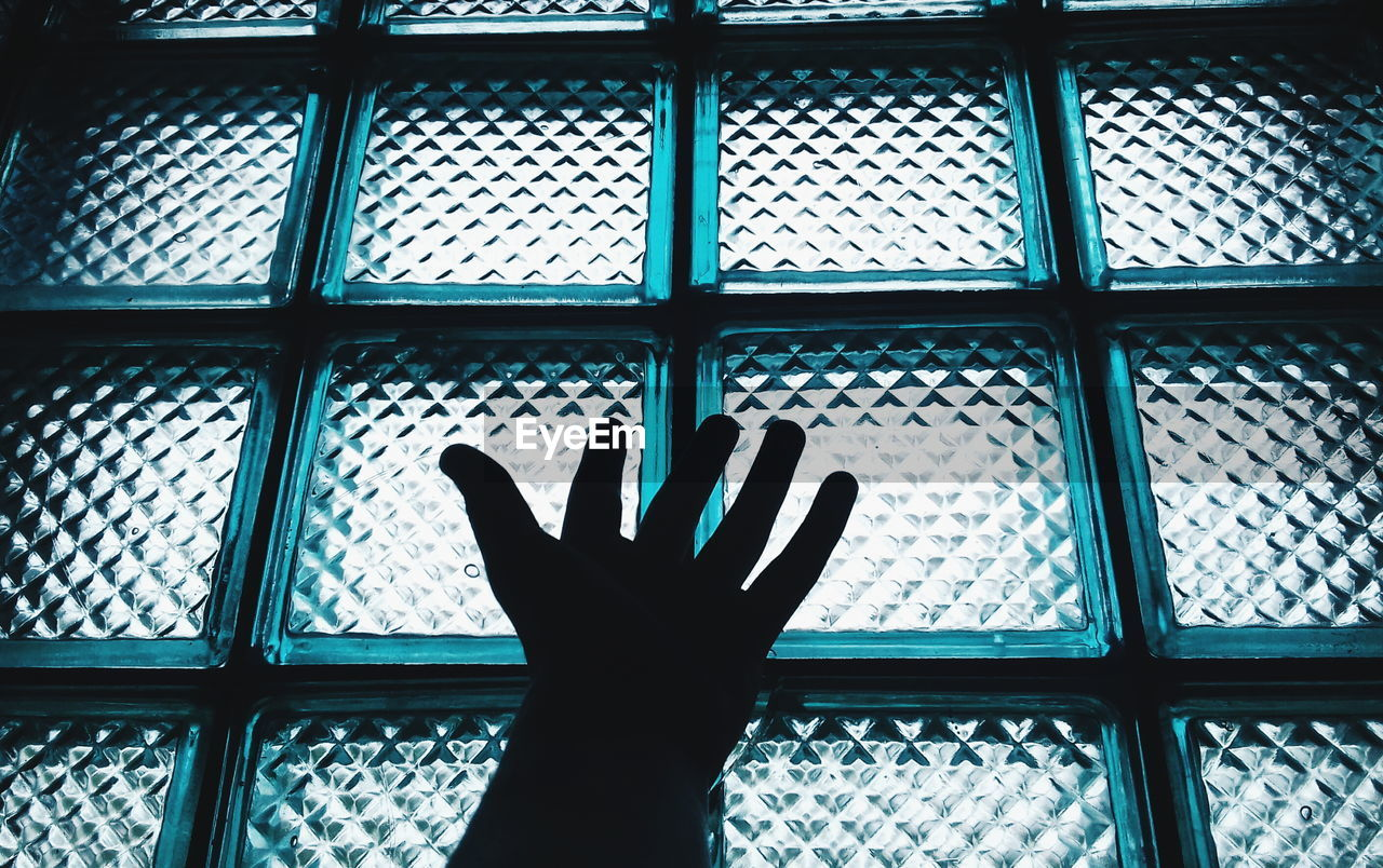 Cropped Image Of Hand Against Glass Window