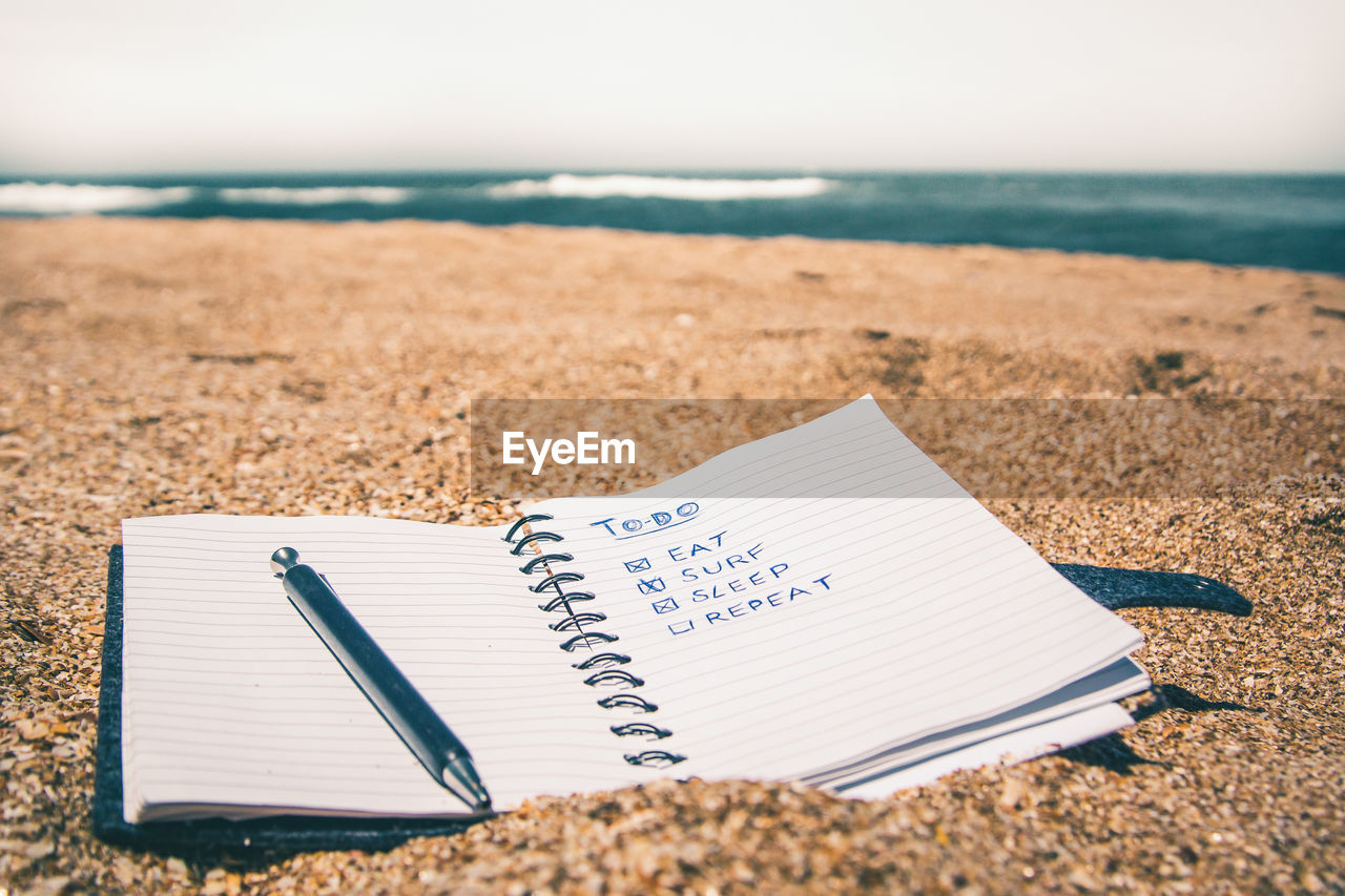 Close-Up Of Spiral Notebook With Pen On Sand At Beach Against Sky