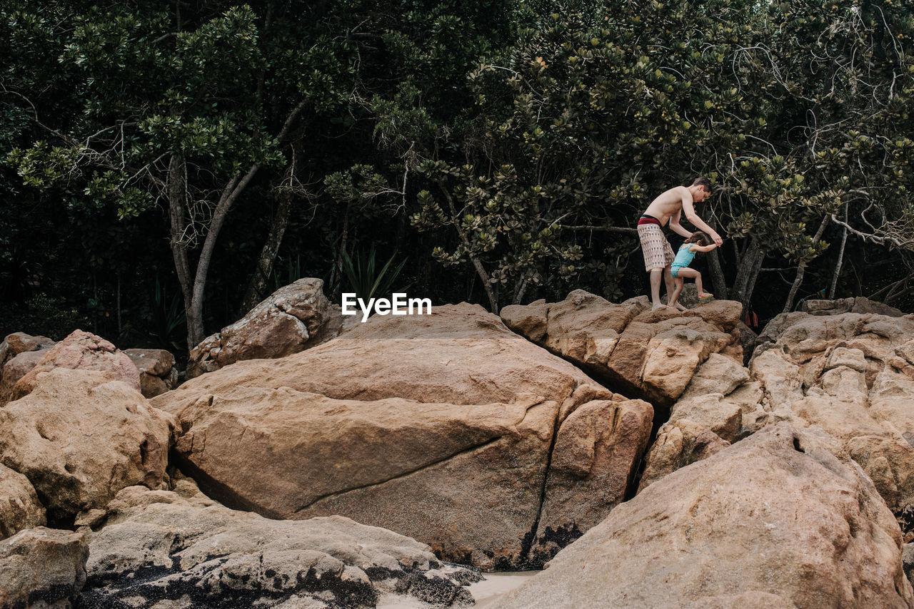 Shirtless Father Helping Daughter In Walking On Rocks