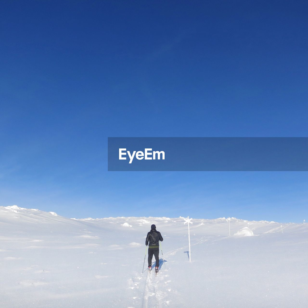 Rear View Of Man Skiing On Snow Covered Mountain Against Clear Sky