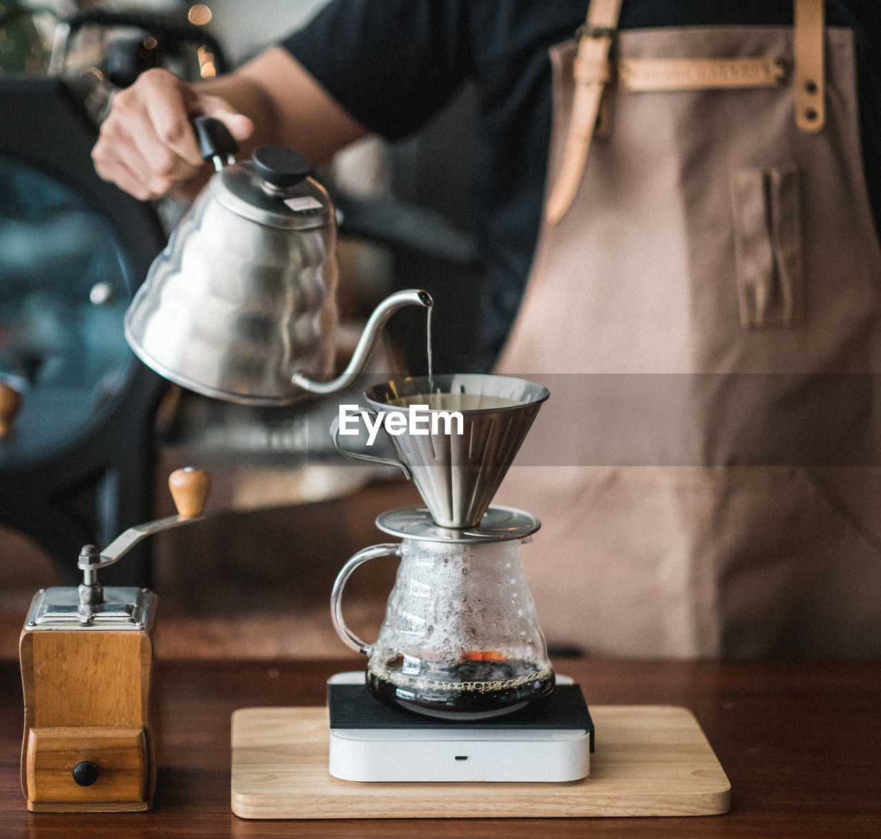 Midsection Of Barista Pouring Coffee In Jar On Table