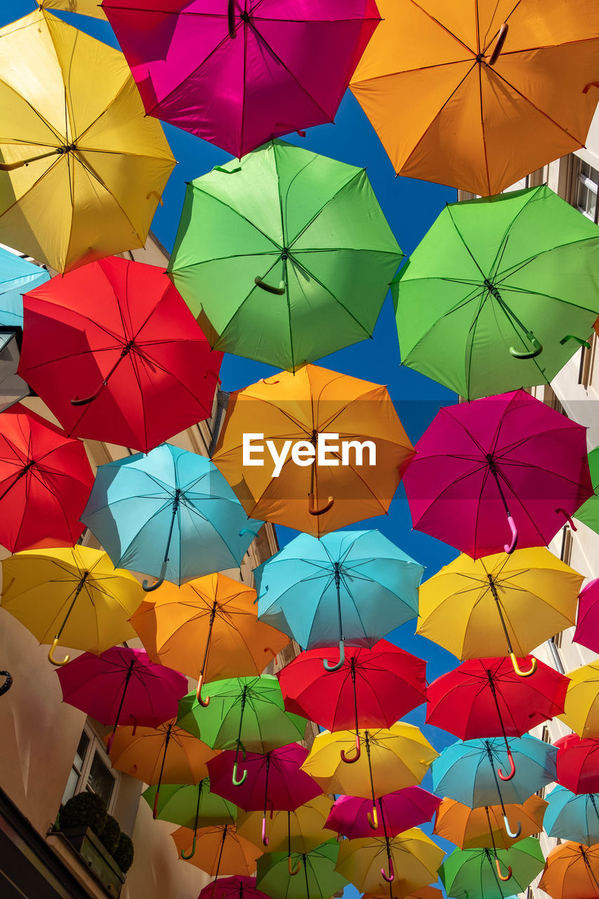 LOW ANGLE VIEW OF UMBRELLAS HANGING ON CLOTHESLINE