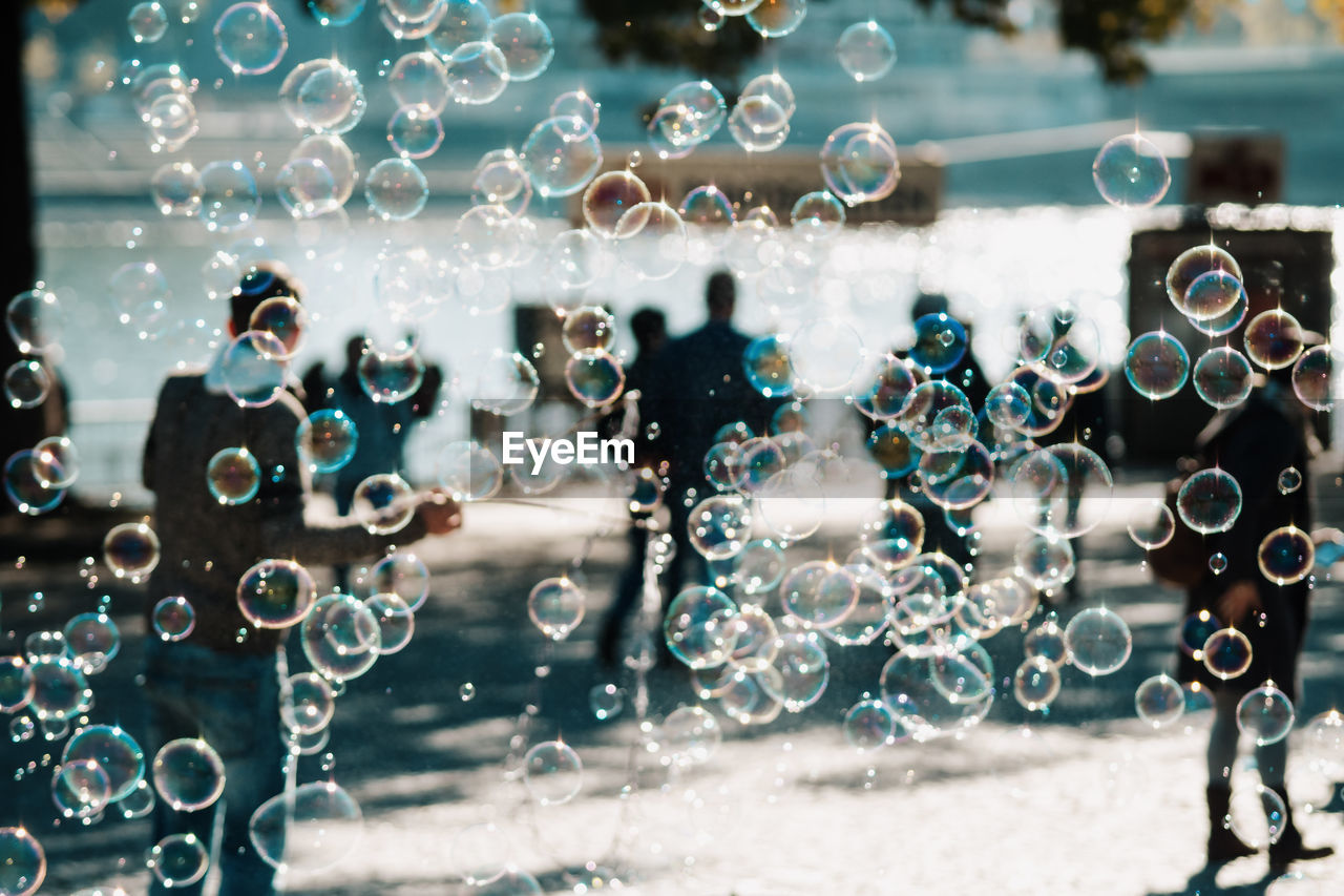 Bubbles And People On Footpath During Sunny Day