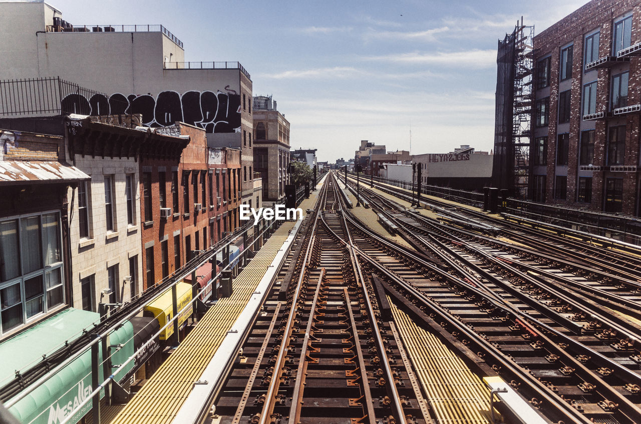 High angle view of railroad tracks amidst buildings against sky in city