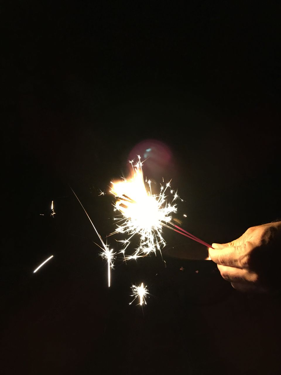 human hand, hand, firework, illuminated, celebration, motion, event, night, human body part, sparkler, burning, holding, arts culture and entertainment, long exposure, glowing, real people, blurred motion, one person, sparks, firework - man made object, firework display, finger, body part, outdoors, dark