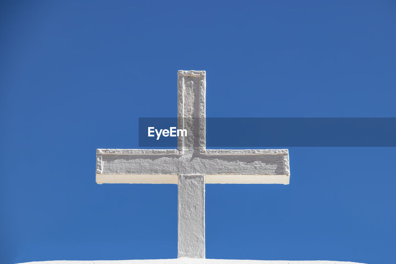 blue, cross, religion, clear sky, low angle view, sky, no people, spirituality, belief, day, nature, cross shape, copy space, outdoors, sunlight, shape, cut out, design