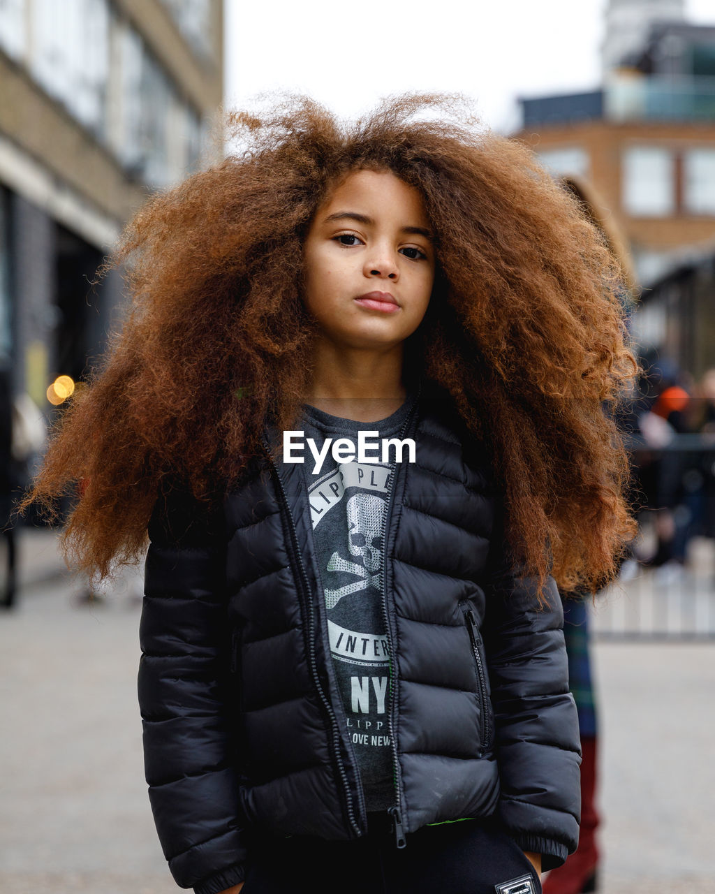 one person, lifestyles, real people, portrait, clothing, standing, front view, jacket, focus on foreground, leisure activity, winter, curly hair, hairstyle, city, looking at camera, hair, architecture, warm clothing, young adult, beautiful woman, outdoors, leather, teenager