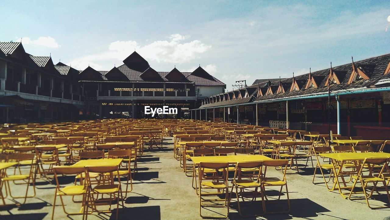 chair, outdoor cafe, table, in a row, empty, outdoors, day, sky, large group of objects, architecture, building exterior, no people