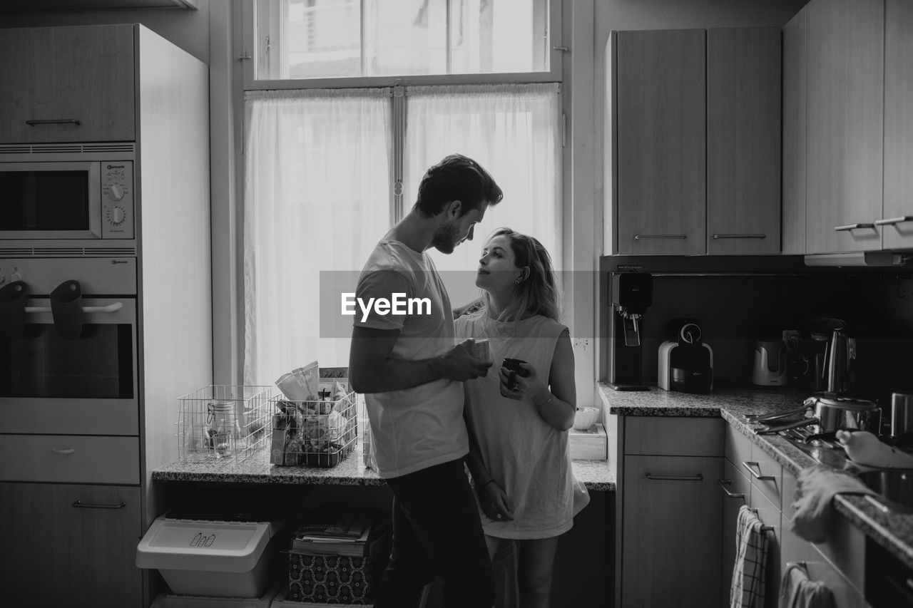 Couple Standing In Kitchen At Home