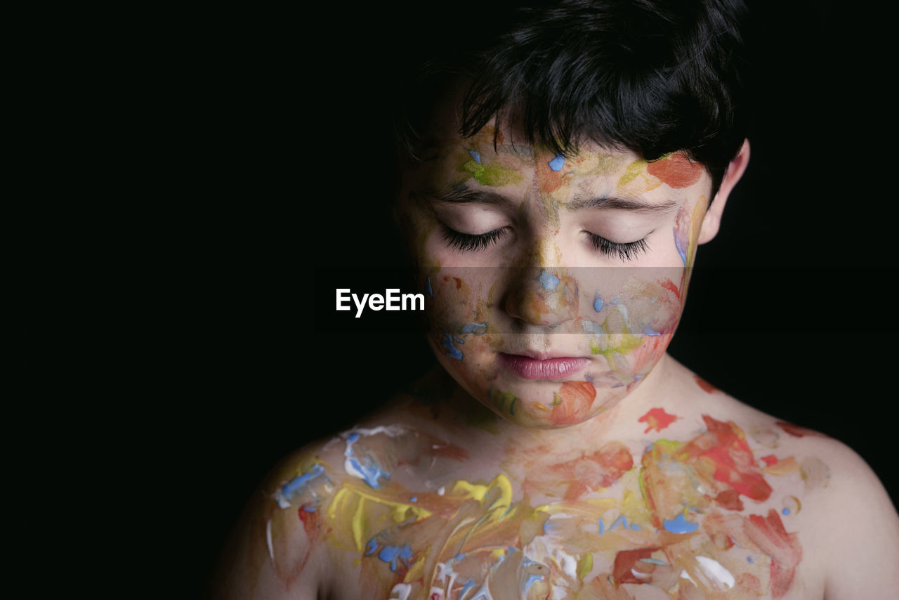 Close-Up Of Shirtless Boy With Colorful Paint Against Black Background