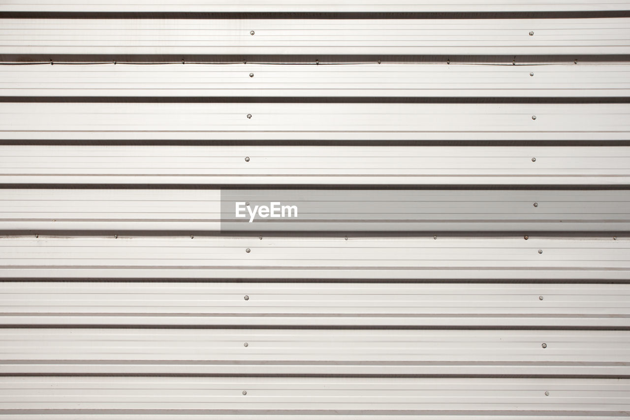 full frame, backgrounds, pattern, shutter, metal, no people, repetition, corrugated iron, iron, security, wall - building feature, safety, textured, closed, wood - material, protection, close-up, indoors, striped, day, corrugated, iron - metal, textured effect, silver colored, garage