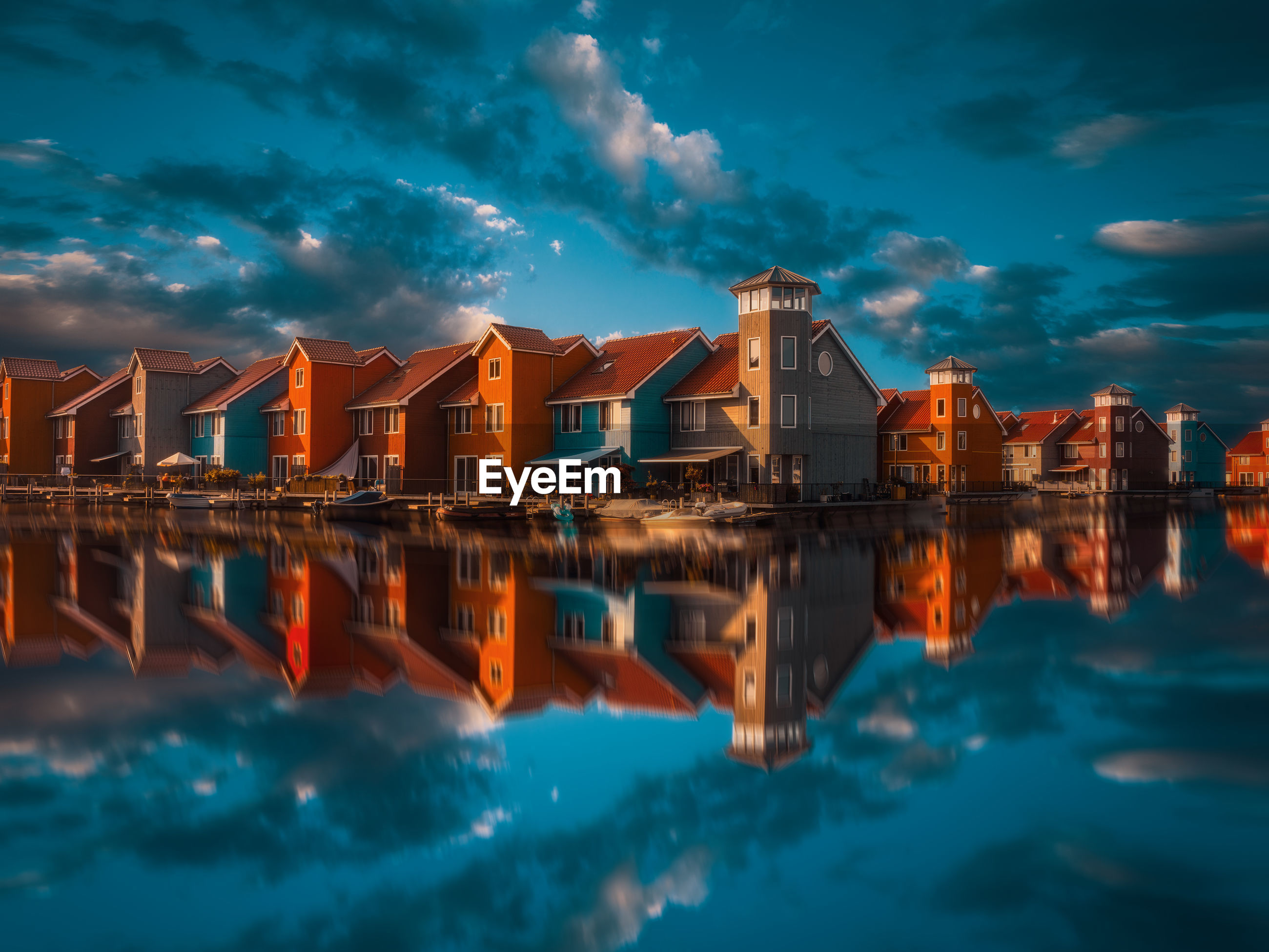 REFLECTION OF BUILDINGS IN SEA AGAINST SKY