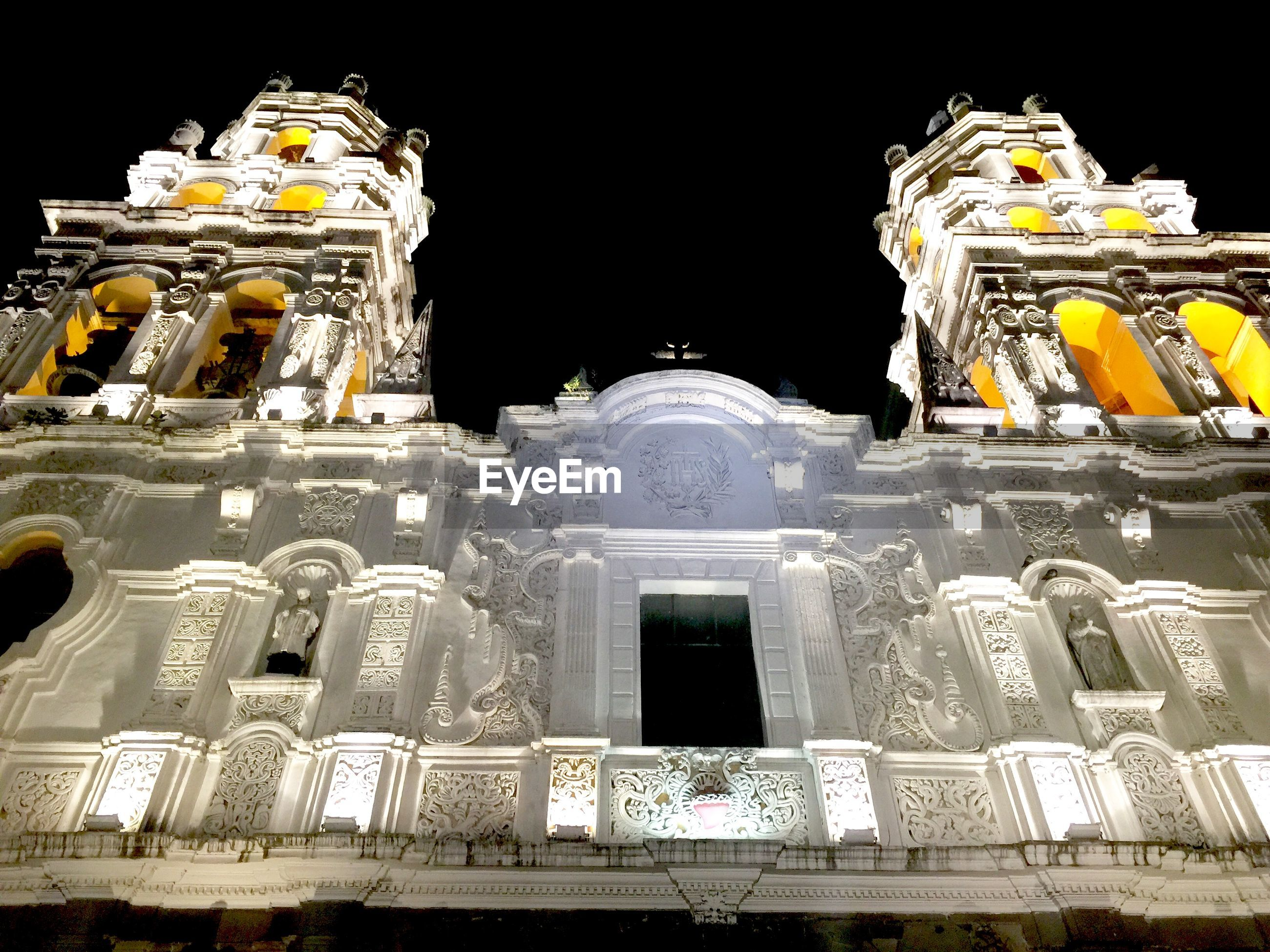 Low angle view of illuminated puebla cathedral at night
