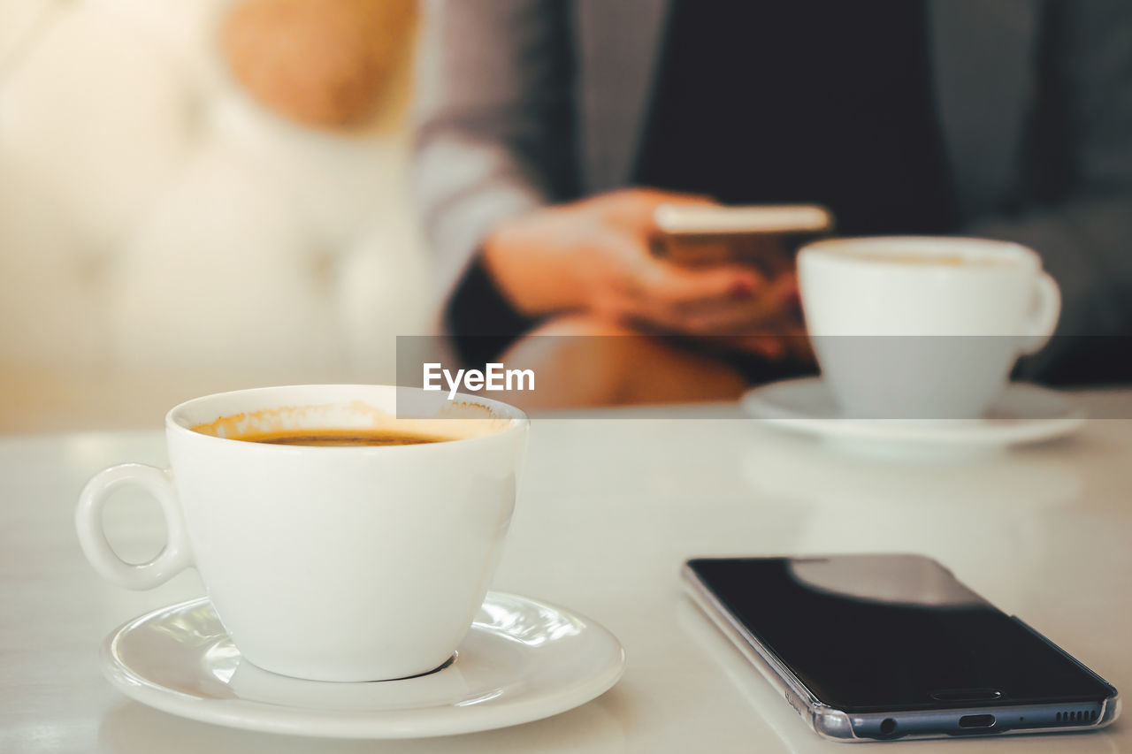 coffee cup, mug, coffee - drink, drink, cup, coffee, technology, food and drink, wireless technology, refreshment, crockery, table, saucer, communication, portable information device, one person, smart phone, mobile phone, focus on foreground, connection, hand, hot drink, coffee shop