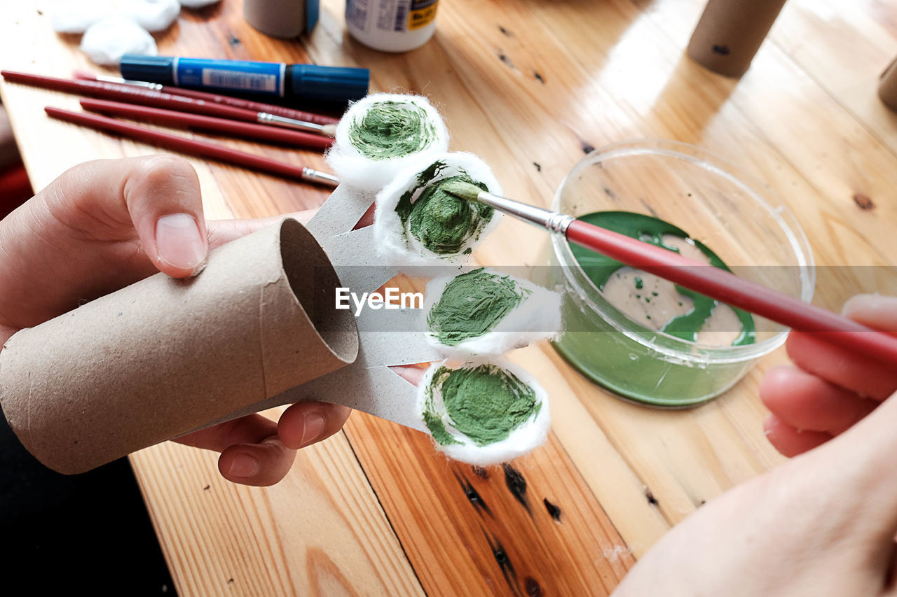human hand, hand, real people, human body part, holding, unrecognizable person, one person, indoors, high angle view, food, lifestyles, food and drink, table, wood - material, personal perspective, body part, preparation, human finger, finger, preparing food