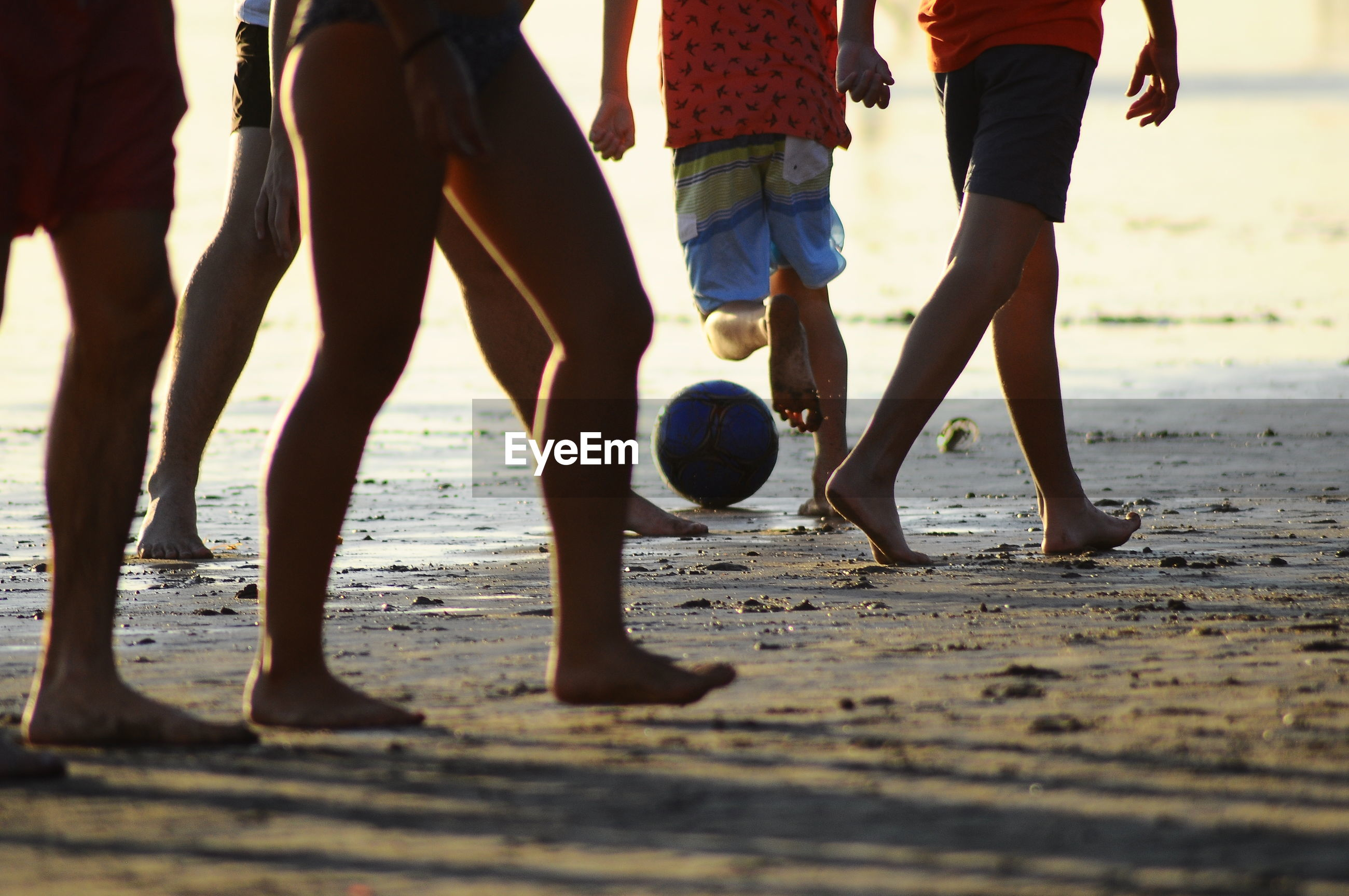 Low section of people playing soccer ball on beach
