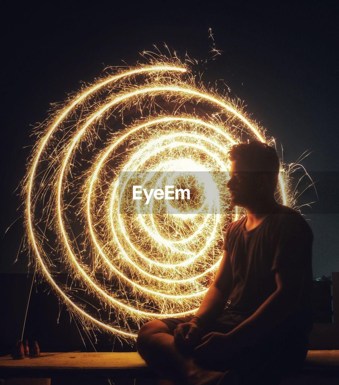 Man Sitting Against Sparkler At Night