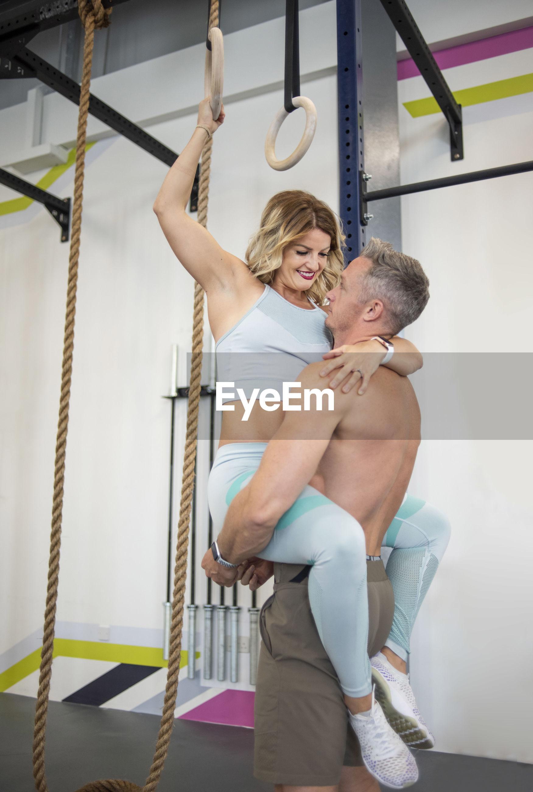 Shirtless man lifting woman at gym
