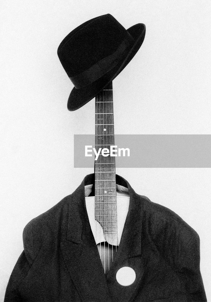 Close-Up Of Hat And Suit On Guitar Against White Background