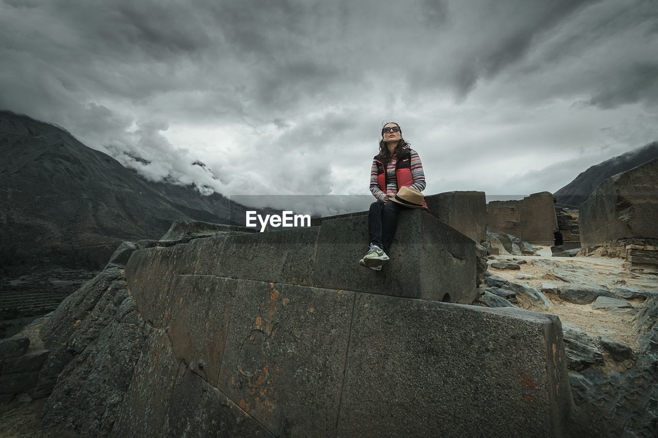 real people, front view, one person, cloud - sky, leisure activity, casual clothing, standing, mountain, full length, lifestyles, outdoors, young adult, sky, day, nature, young women, warm clothing, looking at camera, winter, cold temperature, mountain range, beauty in nature, portrait, people