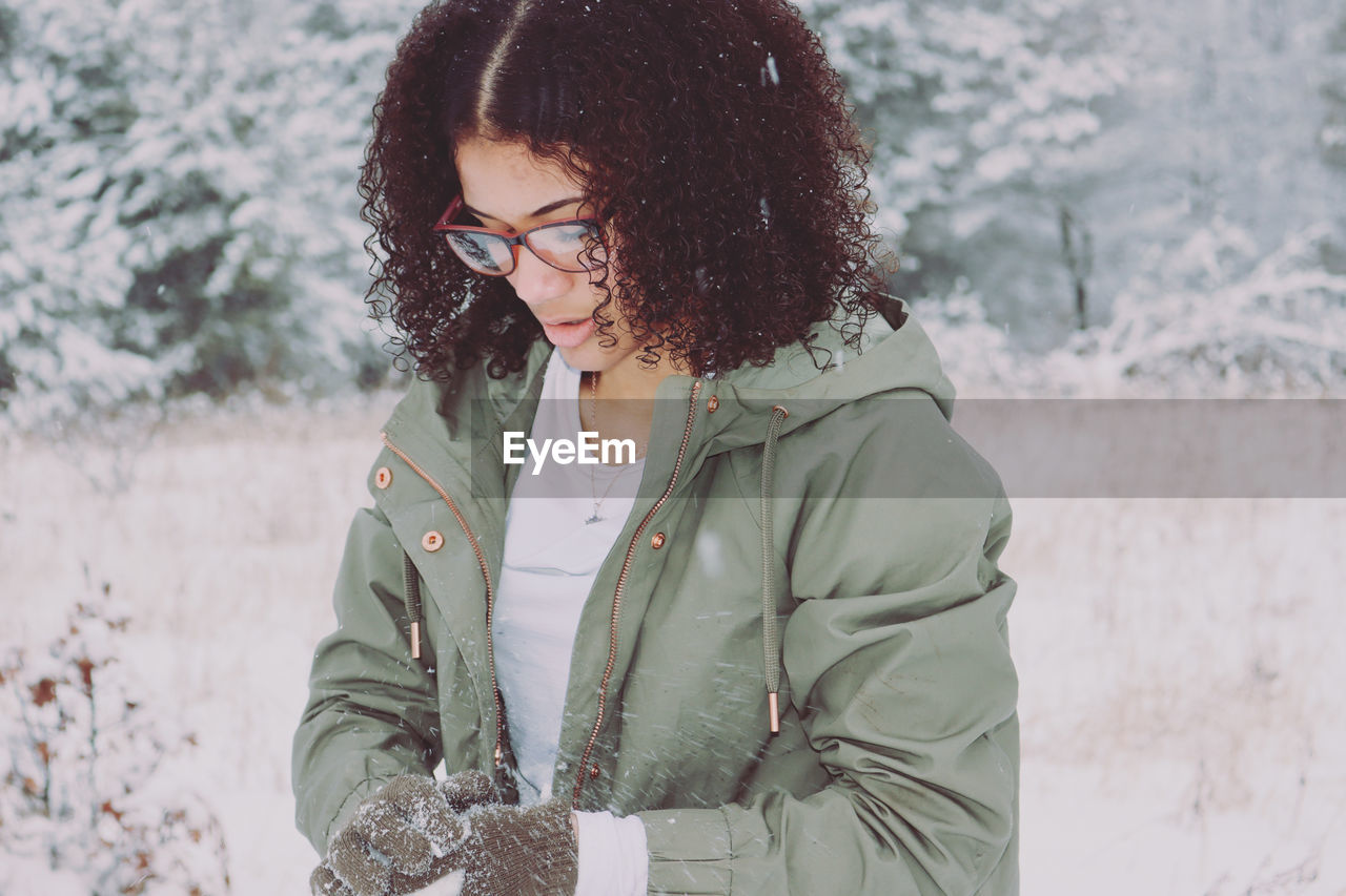 Young woman wearing warm clothing standing outdoors during winter