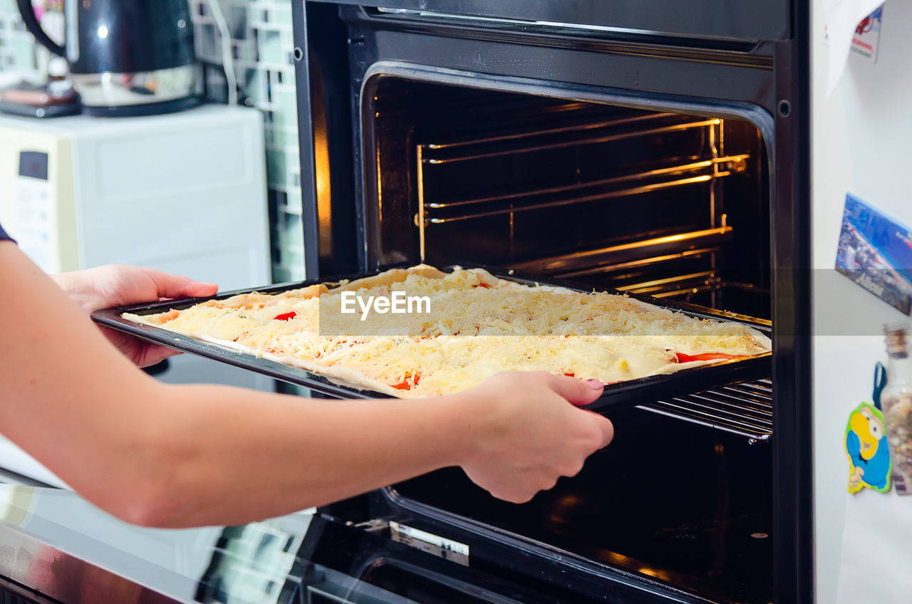 Cropped Image Of Woman Keeping Food In Microwave