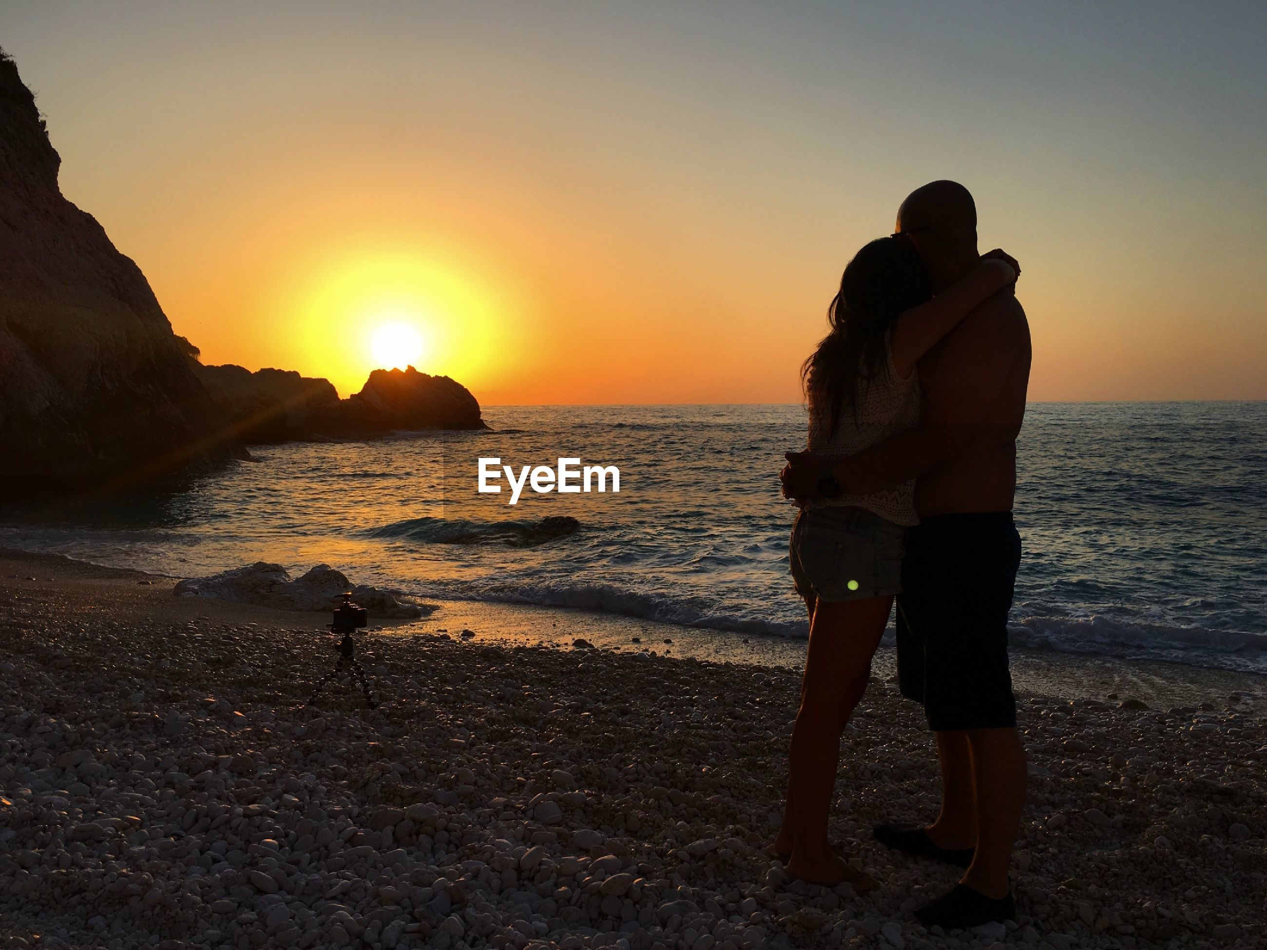 Side view of couple embracing while standing on shore at beach against sky during sunset