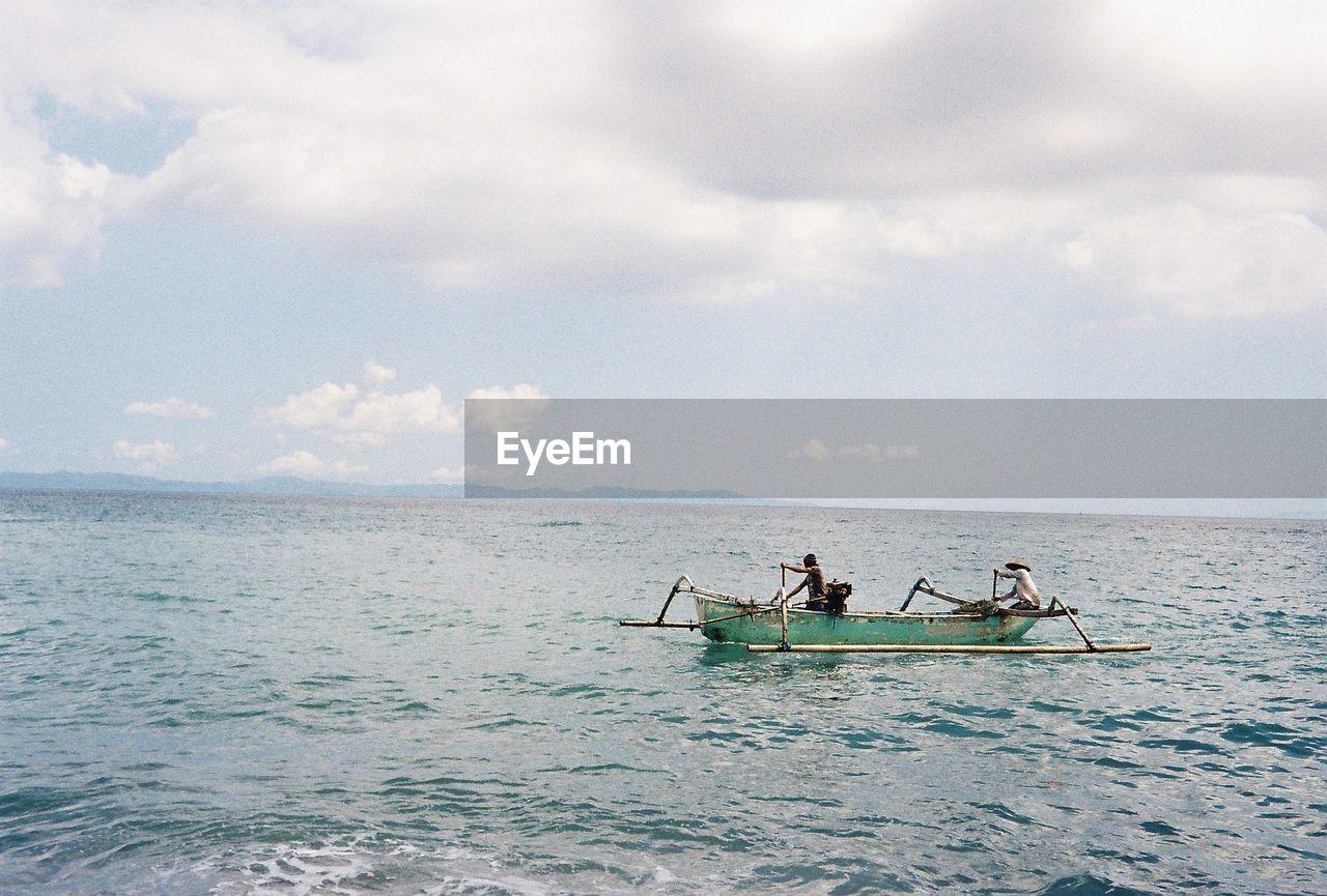 Men In Sailing Boat On Sea Against Sky