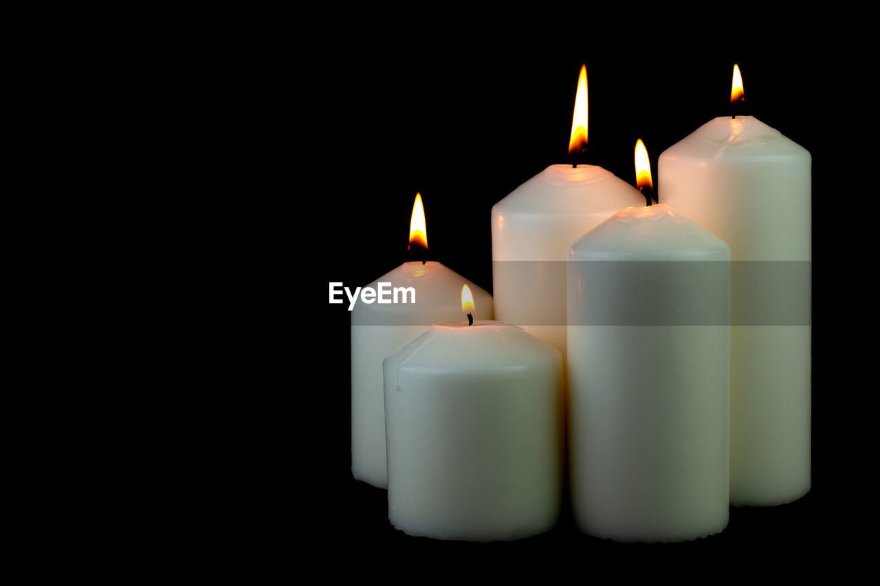 Close-up of lit candles against black background