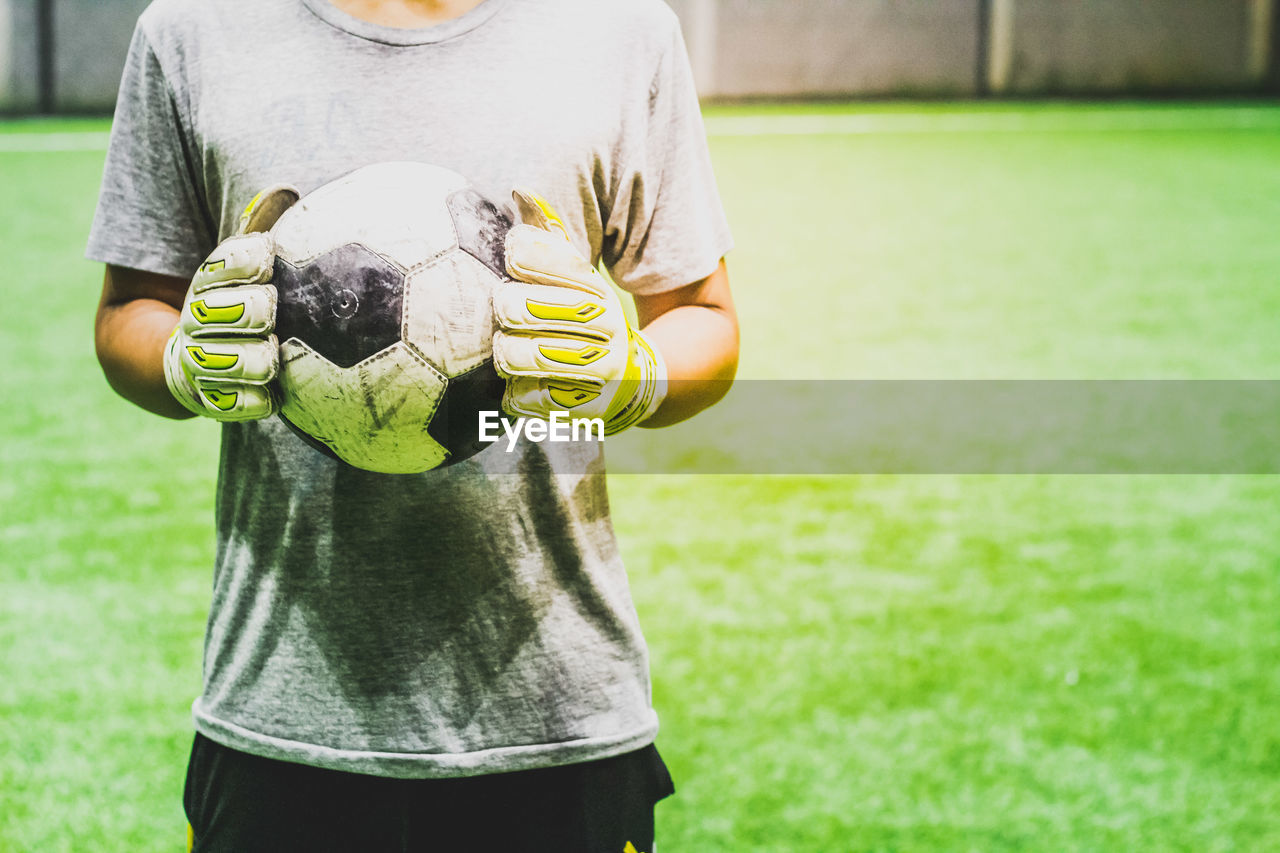 Midsection of man holding ball while standing on grass