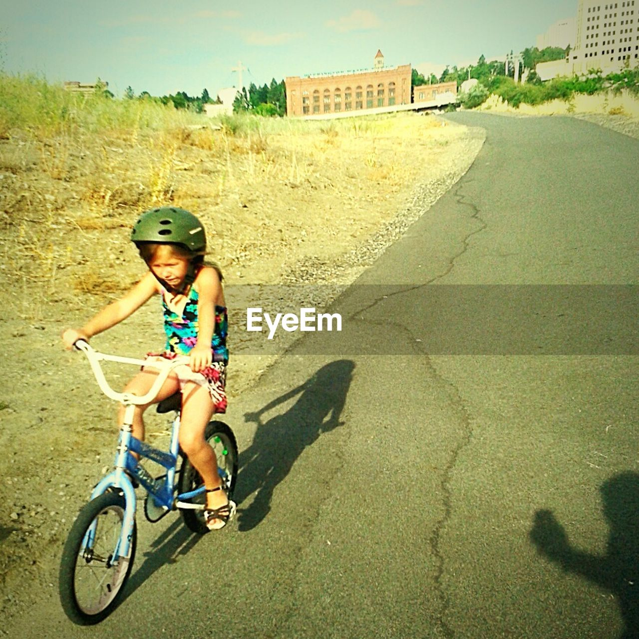 full length, shadow, sitting, one person, sunlight, riding, helmet, leisure activity, headwear, day, outdoors, childhood, architecture, real people, cycling helmet, young adult, sky, people, adult