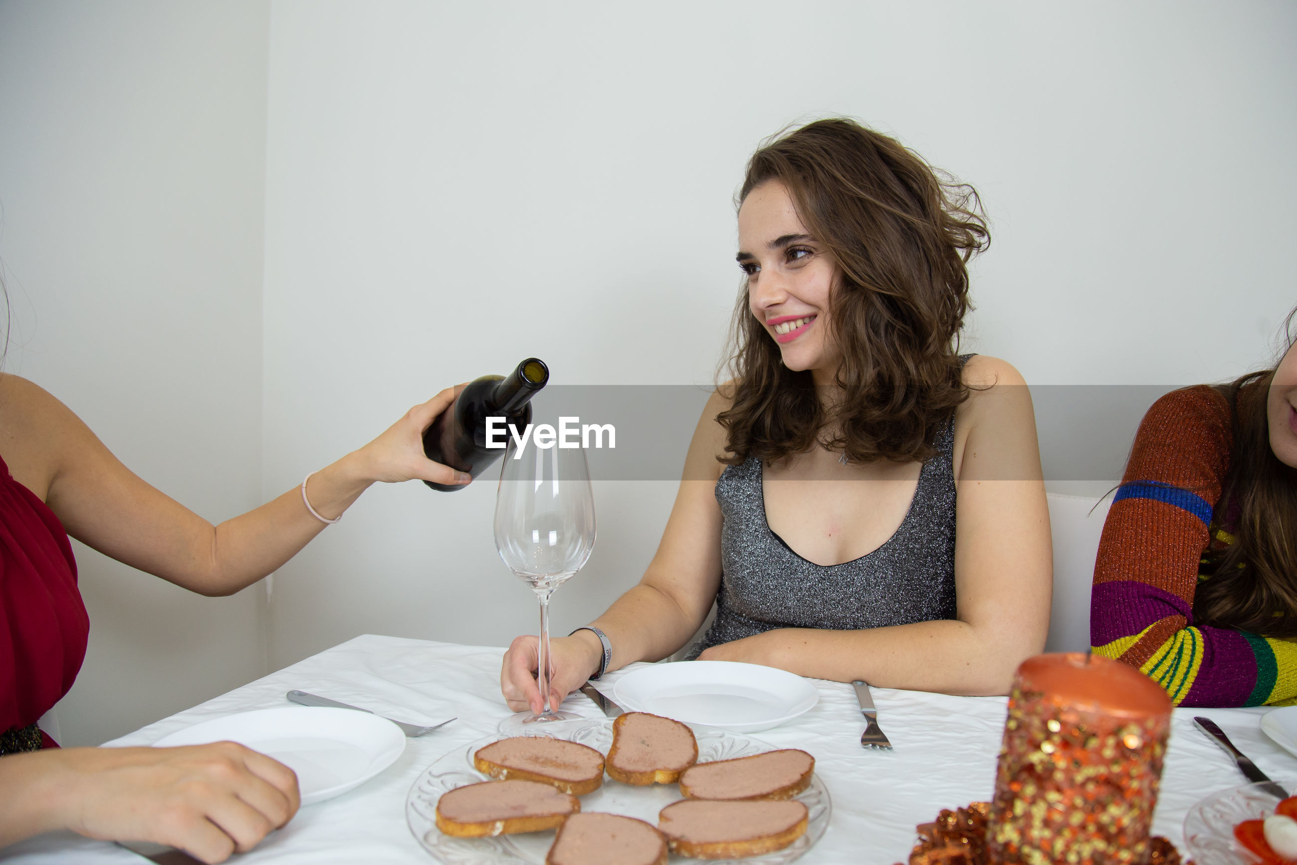 Woman pouring wine in glass by friend sitting on table