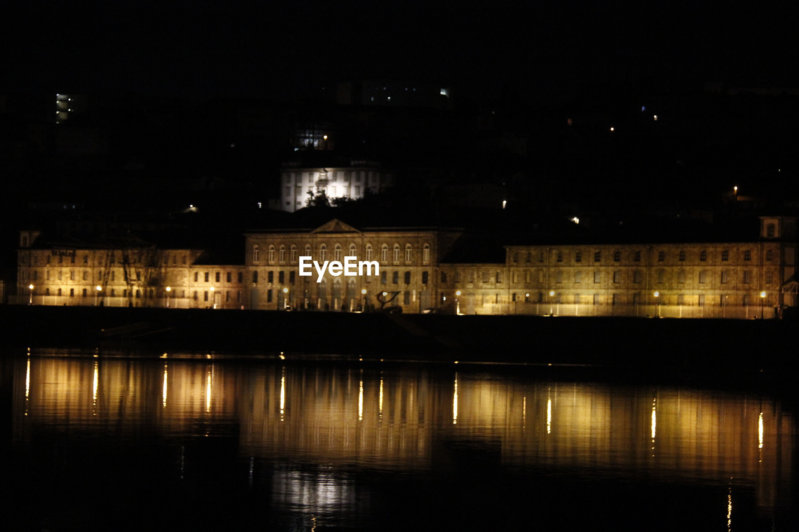 Illuminated historic building by river at night