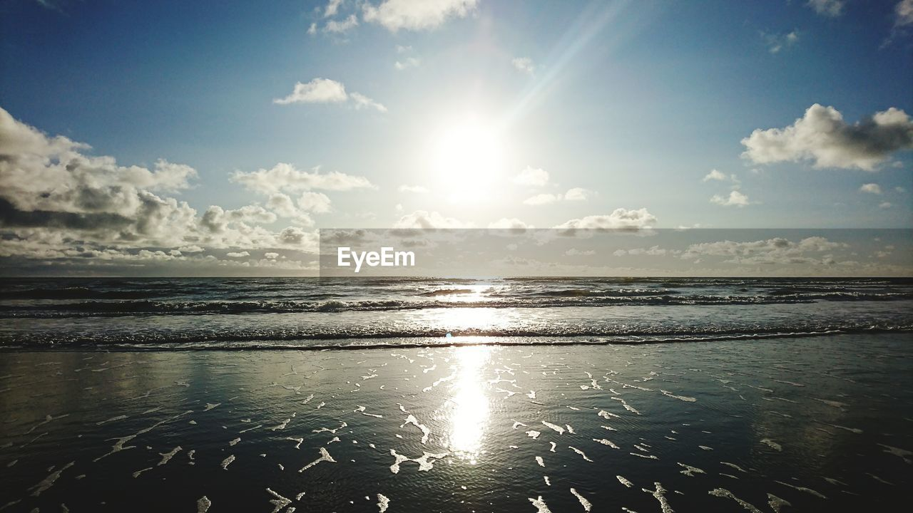 beauty in nature, sea, scenics, sunbeam, sunlight, tranquility, sky, nature, sun, tranquil scene, water, lens flare, idyllic, outdoors, horizon over water, no people, beach, cloud - sky, sunset, day