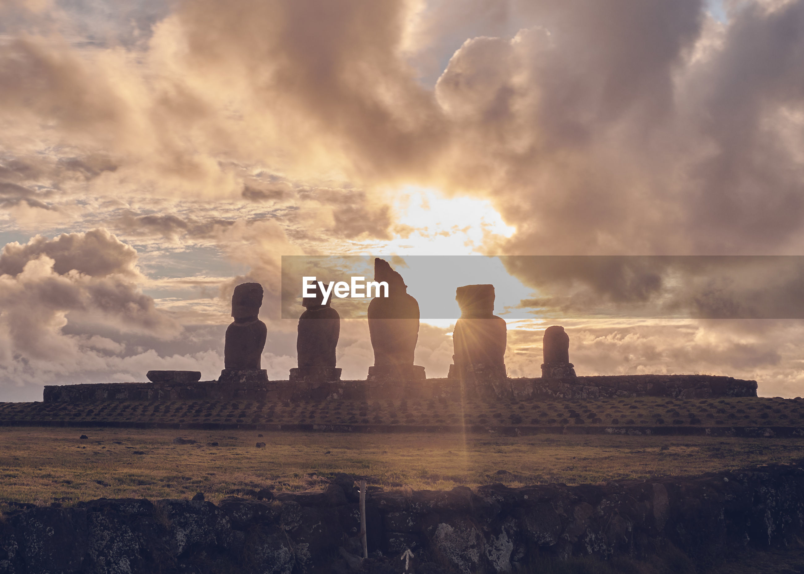 Silhouette of moai statues at sunset on easter island chile