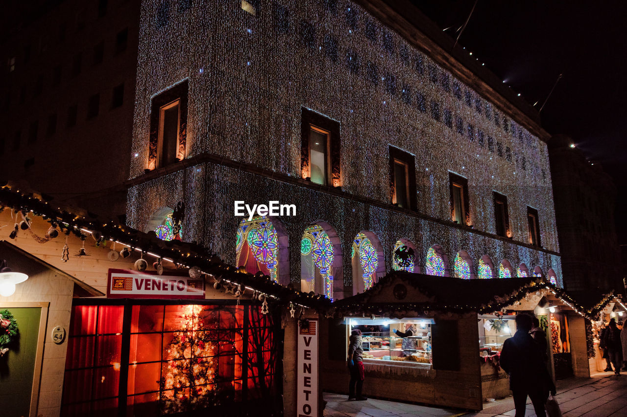 architecture, built structure, building exterior, illuminated, night, building, city, text, low angle view, incidental people, communication, outdoors, multi colored, lighting equipment, western script, real people, window, men, store, decoration