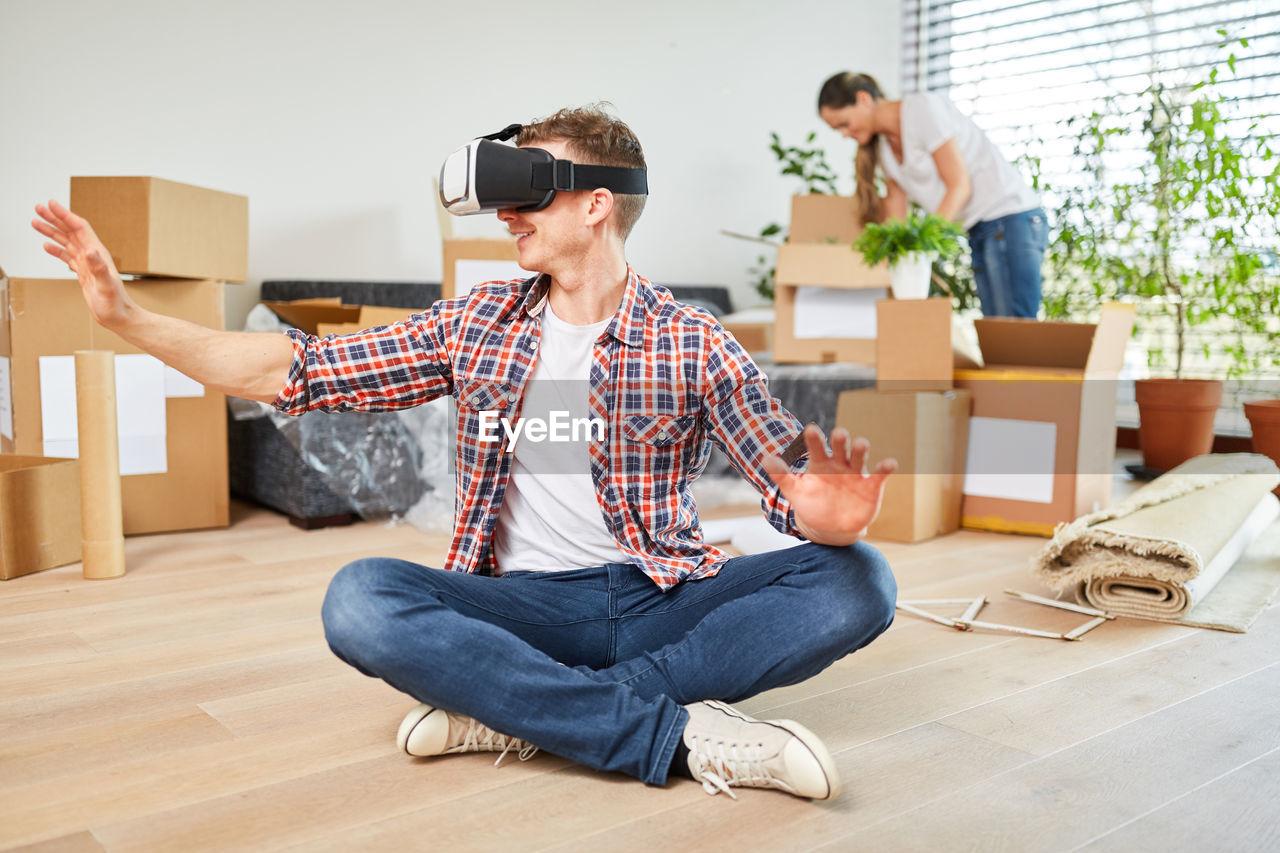 Full length of man using virtual reality simulator at home