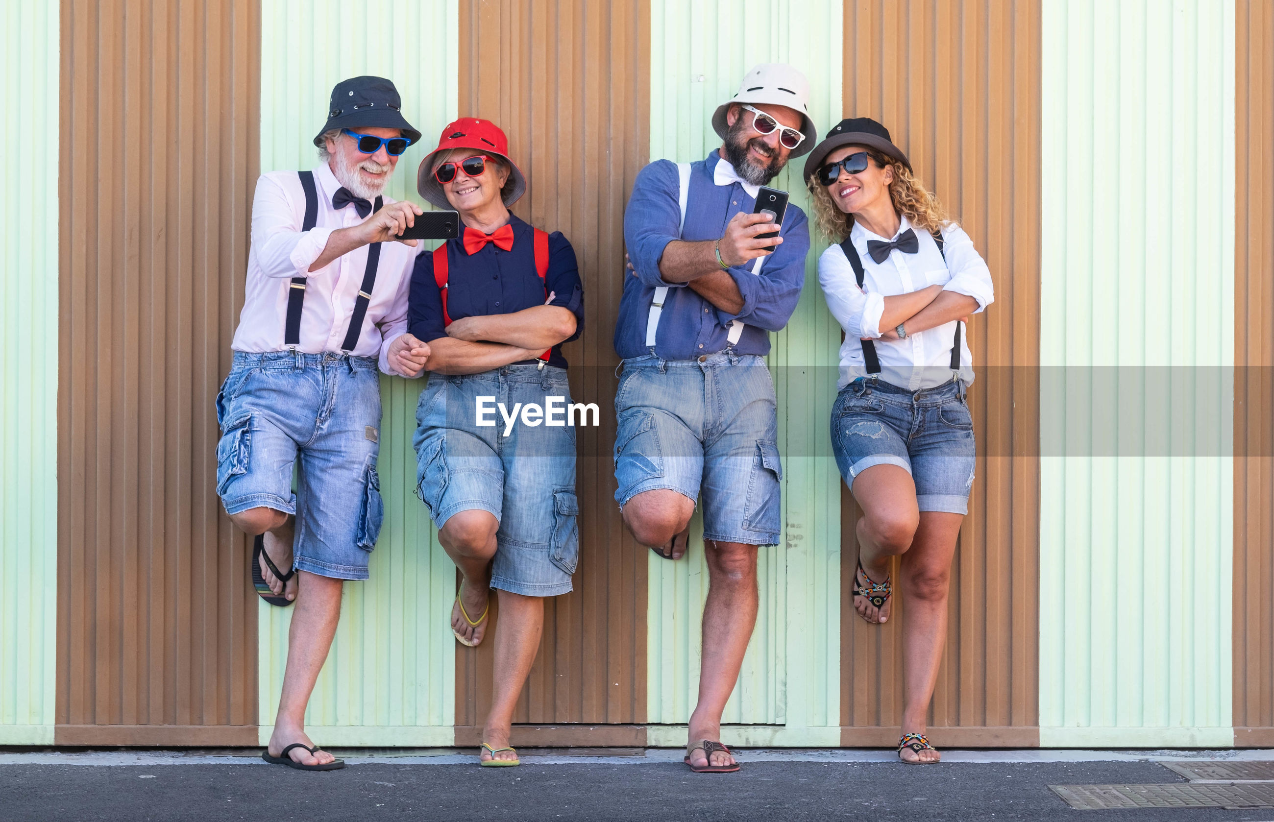 Smiling family using mobile phone while standing against corrugated iron